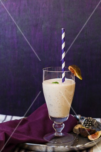 A fig shake in a glass with a straw