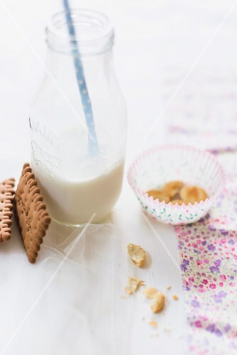 A milk bottle with a straw with butter biscuits and crumbs it
