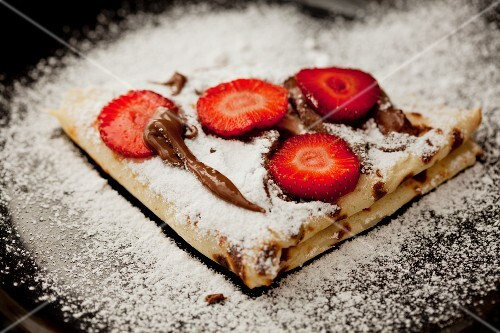 Crepes with chocolate sauce and strawberries