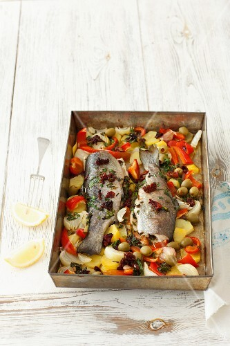 Baked trout with herbs, butter and vegetables on a baking tray