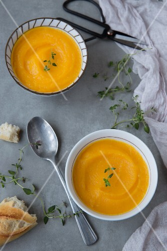 Two bowls of cream of pumpkin soup with thyme and baguette