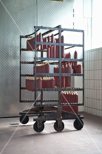 Game sausage hanging on a rack in a butcher's