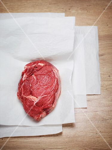 Raw ox steak on a piece of white paper
