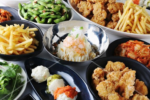 Various party dishes: fried chicken, soya beans, chips and kimchi
