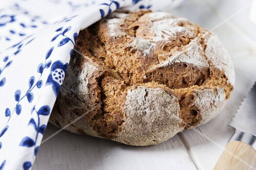 Country bread partially hidden under a floral-patterned cloth