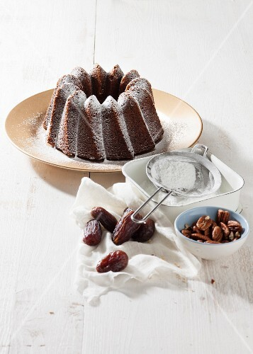 Bundt cake with dates, pecan nuts and icing sugar