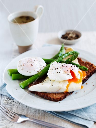 A slice of bread topped with haddock, poached egg and asparagus