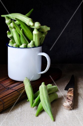 Okra pods in an enamel mug