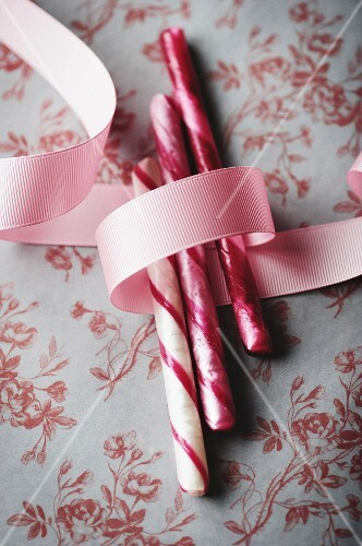 Candy canes with a pink ribbon on a floral-patterned surface