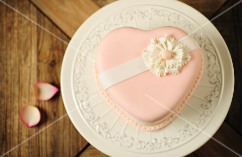 A pink, heart-shaped marzipan cake on a cake stand (seen from above)