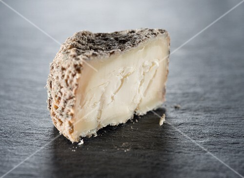 A slice of goat's cheese on a slate surface