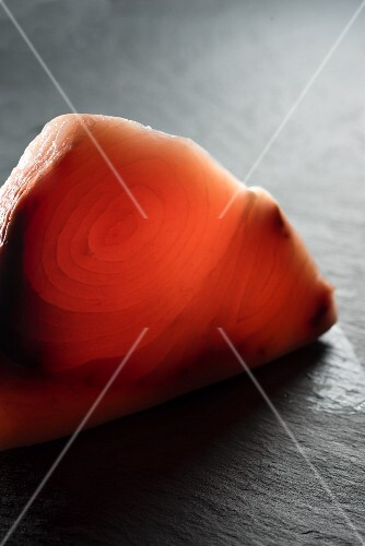 A raw swordfish steak on a slate surface