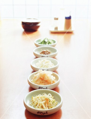 Five Korean side dishes in white bowls with soy sauce, salt and chilli powder in the background