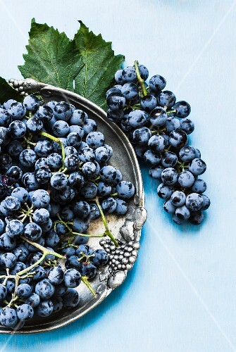 Blue grapes on a metal plate and next to it