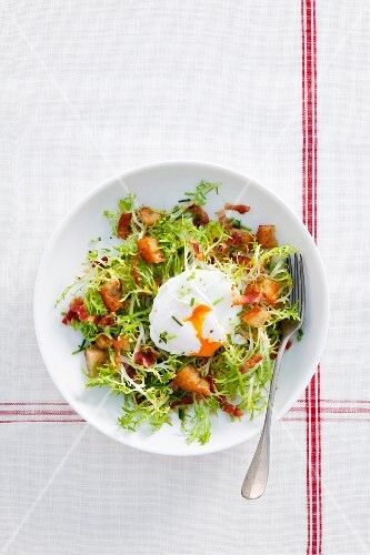 A poached egg on frisee lettuce with bacon and croutons