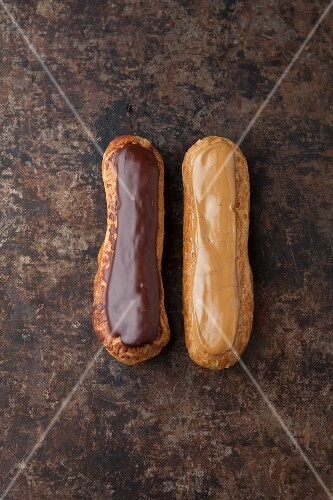 Two éclairs one with chocolate glaze and one with coffee glaze on a baking tray