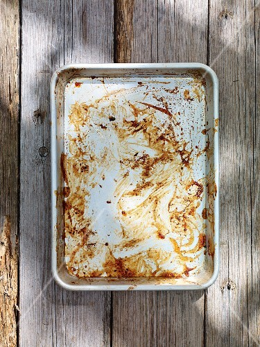Remains of gravy in a roasting tin on a wooden table
