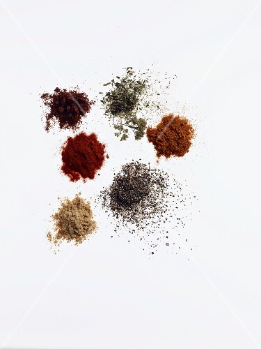 Six different piles of spices for making a dry marinade