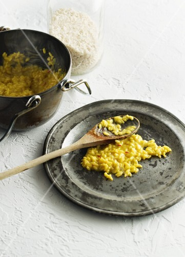 Risotto alla milanese on a plate with a wooden spoon and in a pot
