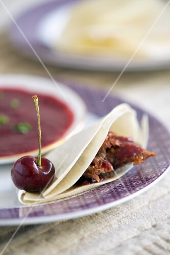 A crepe filled with duck with a spicy cherry sauce