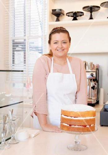 A proud baker presenting a three-layered cake