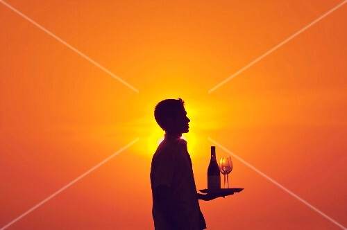 A waiter holding a bottle of wine and two glasses on a tray at sunset