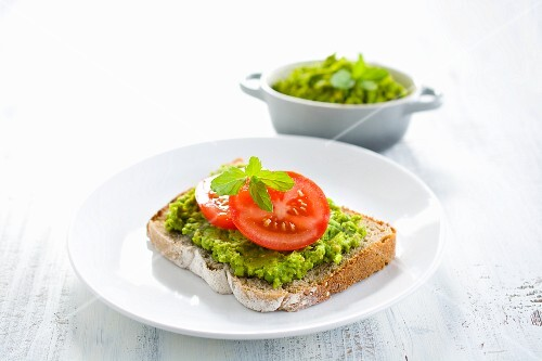 A slice of bread topped with a pea spread and tomatoes