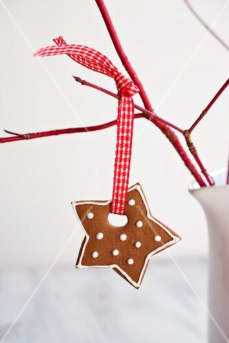 A gingerbread star hanging from a twig