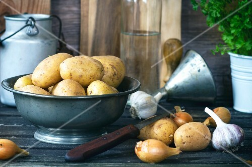 Potatoes in a metal bowl next to onions and garlic on an old wooden table