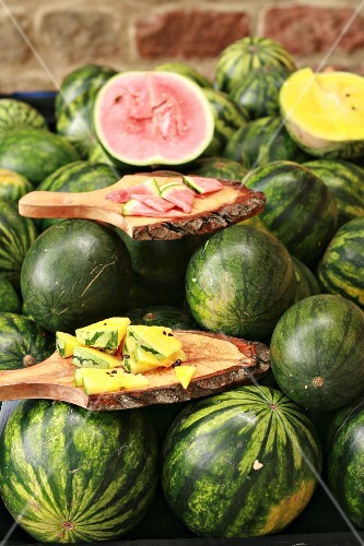 Red and yellow watermelon on a market stand
