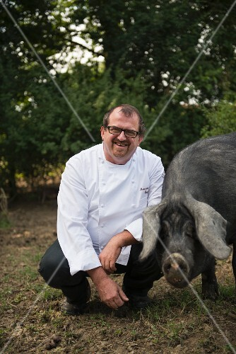 Head chef Massimo Spigaroli with a black pig at his Antica Corte Pallavicina