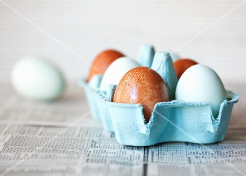 A box of brown and pastel blue eggs