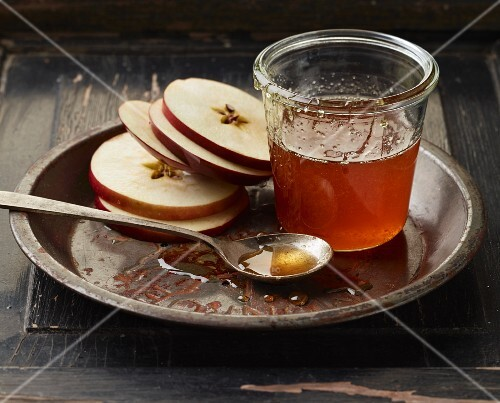 Apple slices with honey on a metal plate