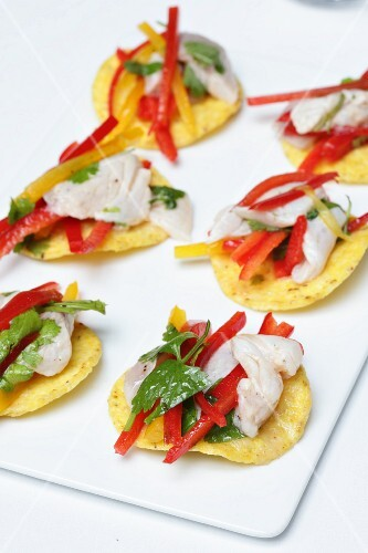 Potato crisps topped with fish, pepper strips and parsley