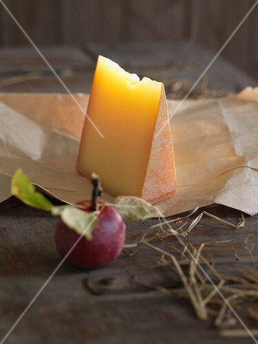 Mountain cheese and an apple with a bite taken out of it on a wooden surface