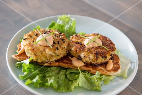 Fried lobster cakes on a bed of lettuce