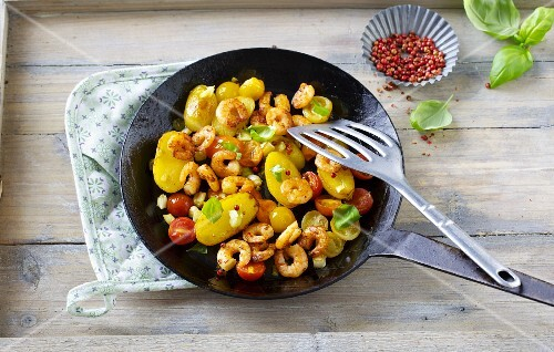 Fried potatoes and prawns with cherry tomatoes