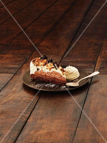 A slice of chocolate brownie cheesecake with cream