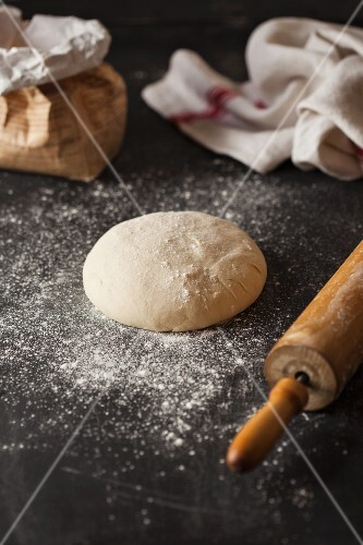 A ball of pastry, a rolling pin, flour and a tea towel