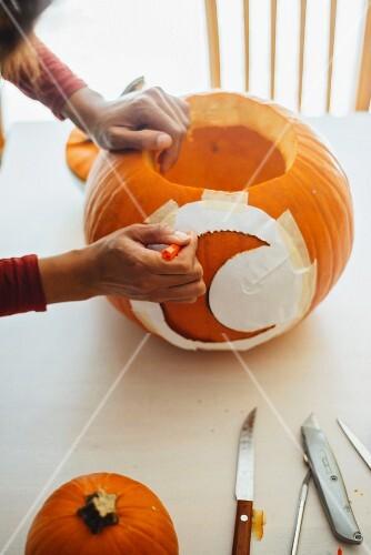 Woman drawing moon motif on Halloween pumpkin