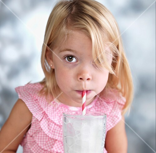 A blonde girl blowing bubbles through a straw into a glass of milk