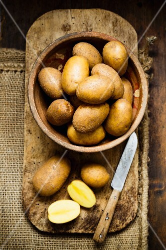 Potatoes in a wooden bowl on a chopping board with a knife