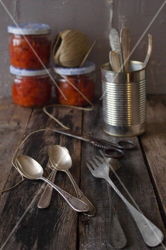 Silver cutlery with tomato sauce in the background