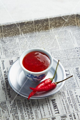 A bowl of chilli chutney on a newspaper