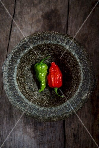 Two fresh chillis in a mortar