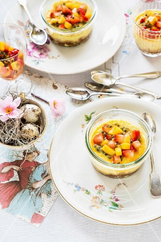 Mini cheesecakes in glass bowls with Spekulatius (German Christmas shortcrust biscuits), mango and strawberries