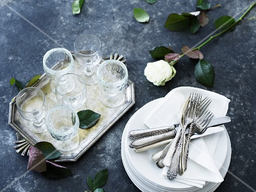 A stack of plates with napkins and cutlery next to glasses and a rose on a tray