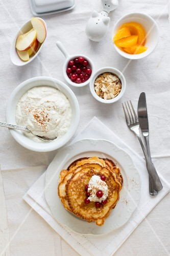 Pancakes with coconut and cinnamon quark, redcurrants, fruit and flaked almonds