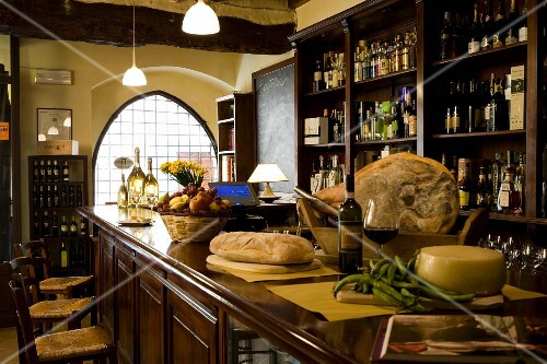 A wheel of cheese and a loaf of bread, wine and Tuscan ham on the bar of an enoteca, Italy