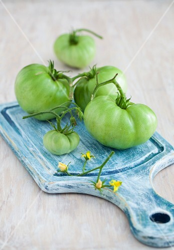 Green tomatoes on a blue chopping board